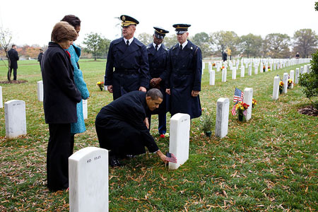 President Obama places a Presidential Coin at Ross McGinnis' gravesite