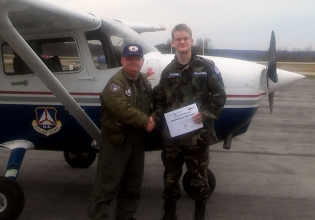 "Photo-02. Suggested Cutline: Cadet Noah Ossman receives his ""First Flight"" certificate from pilot, Master Sergeant Bill Story."